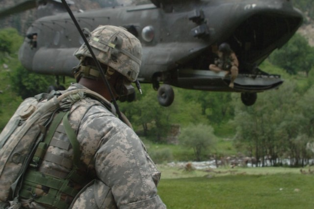 Sgt. 1st Class Malwonte Stewart monitors his radio while a CH-47 Chinook helicopter lands at Paruns.