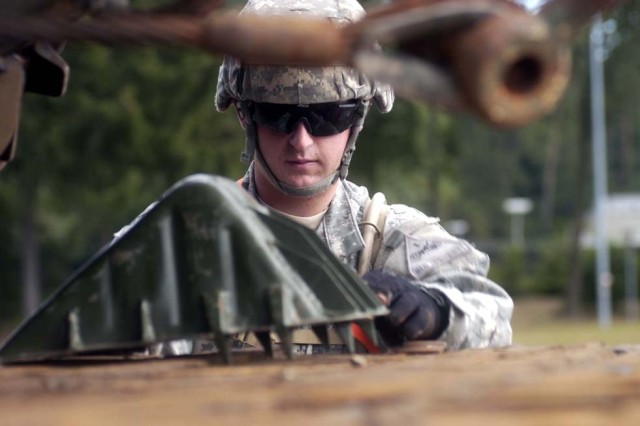 Pvt. Nathaniel Beeghly, 40th Engineer Battalion, places a chock block on a railcar to prevent the wheels on an M-9 Armored Combat Earthmover from moving.