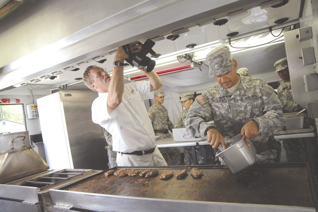 """Jared Manders, photo director for the Food Network's """"The Secret Life Of..."""" records Pvt. Petajan Bozhidar as he works over the grill at the U.S. Army Quartermaster Center and School's Army Center of Excellence, Subsistence Field Operations Training Branch July 12 at Fort Lee, Va."""
