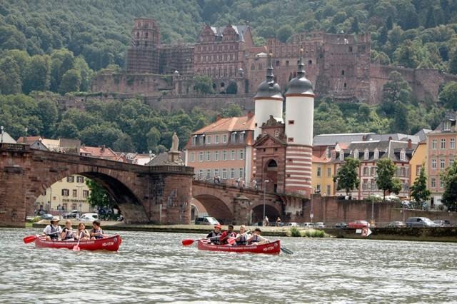 Camp A.R.M.Y. Challenge participants canoe past Heidelberg's AltebrAfA1/4cke and schloss, as part of a week-long city adventure.