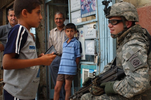 Pfc. Travis Todd chats with residents near a fish market.