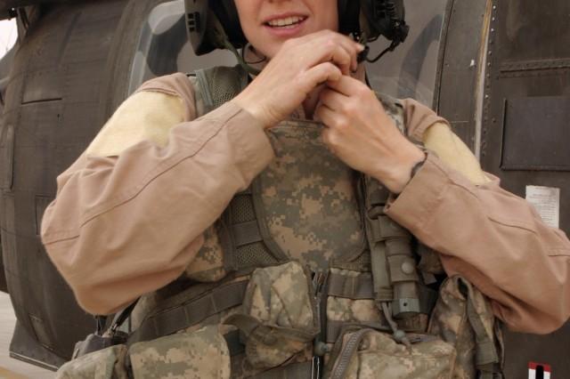 Spc. Megan M. McKinzie, crew chief, suits up for the mission.