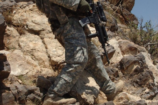 Staff Sgt. Daniel Moncada moves through terrain more suited for mountain goats than humans.