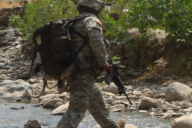 Senior Airman Elvin Blackmon, a medic, uses stepping stones to cross a river.