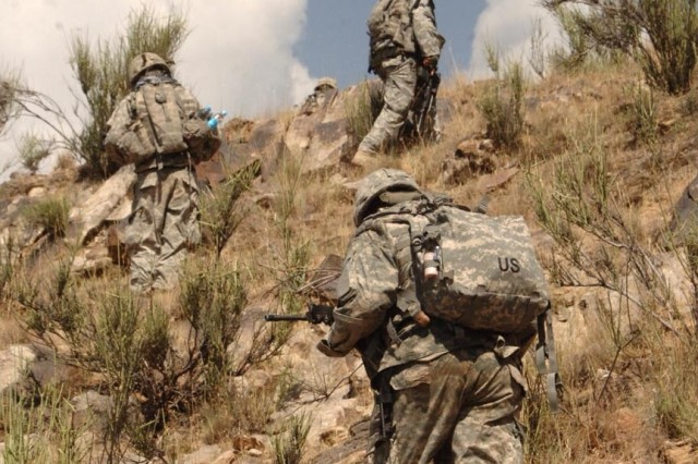 Soldiers scale a ridge.