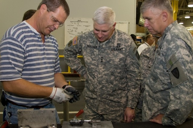 Scott Shaddis, small arms repairer, demonstrates one of the changes, compliments of a process improvement,  on the butt stock of an M249 small arms weapon to Gen. Benjamin Griffin (r)  and Lt. Gen.  David Melcher during a depot visit July 18.