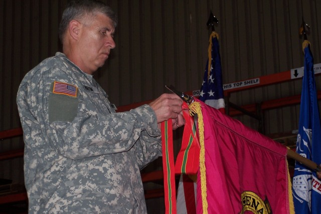 Gen. Benjamin S. Griffin, U.S. Army Materiel Command commanding general, places the Army Superior Unit Award streamer on the Rock Island Arsenal Joint Technology and Manufacturing Center flag during an awards ceremony at the facility. (U.S. Army photo by Galen Putnam).""