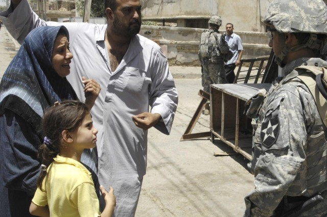 Soldiers interview residents about insurgent activity in the neighborhood.