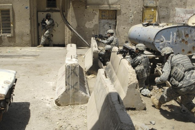 Some Soldiers find good cover and shooting positions behind concrete barriers.