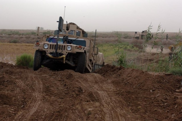 A Humvee traverses the new road. While not the Interstate, it's suitable for tactical vehicles and gets the job done.
