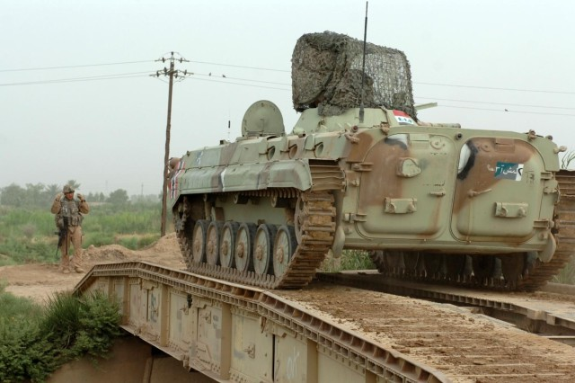 A U.S. Soldier directs an Iraqi infantry fighting vehicle (Soviet-era beovaya mashina podderzhki or BMP) over a mobile bridge built by the sappers.