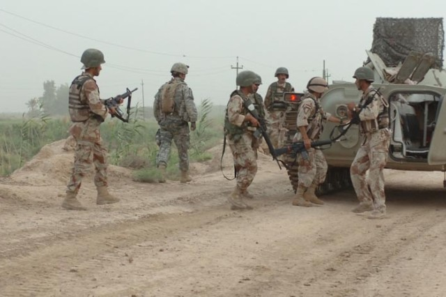 Iraqi Soldiers prepare to get back inside their BMP after a security halt.