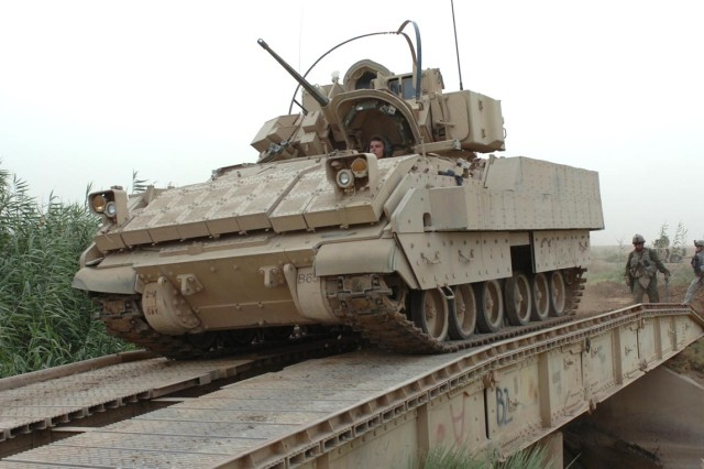 A U.S. Soldier drives a Bradley fighting vehicle over the new bridge.