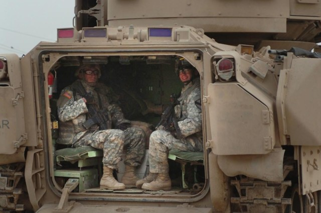 Soldiers in a Bradley fighting vehicle smile for the camera.
