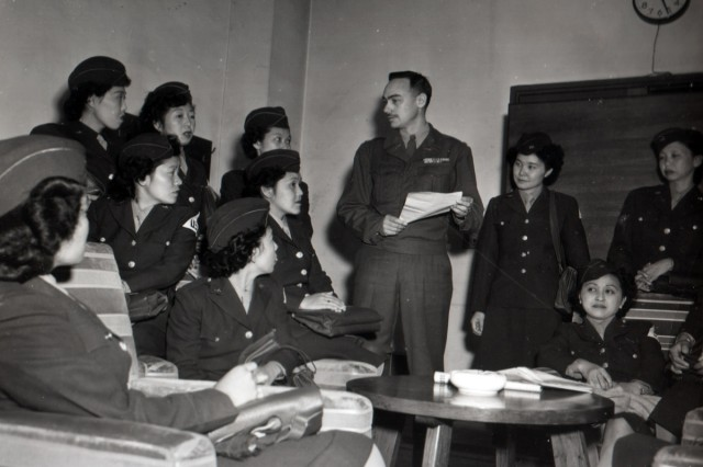 Japanese-American Nisei Soldiers, having just arrived in Tokyo, are briefed by Lt. Col. Chet Wadsworth, Deputy Civil Censorship Officer (center) with whom they will serve at General Headquarters.