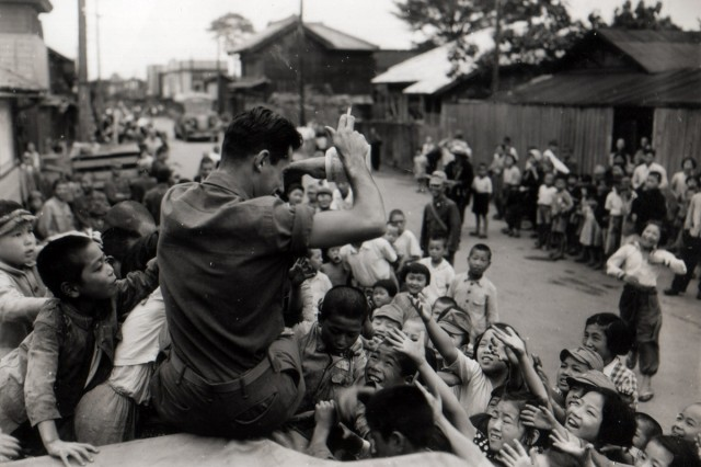 Japanese children crowd around a U.S. Soldier atop of a jeep, as he hands out candy.