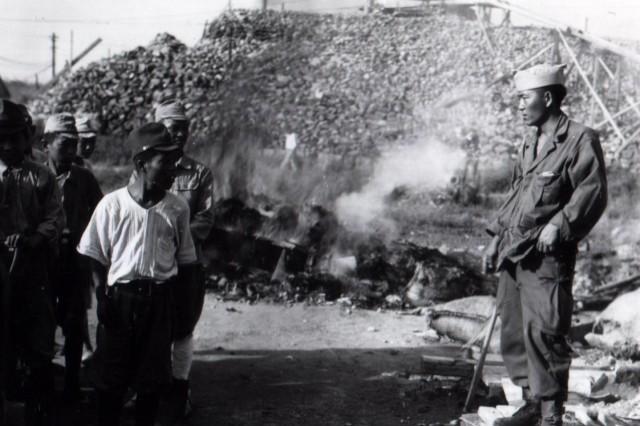 Japanese American Soldier Walter Kajiwara (left) directs Japanese soldiers at work at the 98th Division headquarters at Taisho Airport, Osaka, Japan. (October 2, 1945)