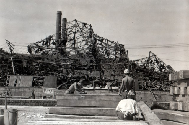 Japanese civilians in Nagasaki, Japan, prepare lumber for rebuilding their home, destroyed by the blast of the atomic bomb.  This area was about a half of a mile from the center of the blast. (September 29, 1945)