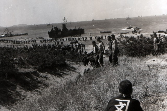 A Japanese civilian watches from a distance as the 130th Infantry, 33rd Division make an amphibious landing at Wakayama, Japan. (September 25, 1945)