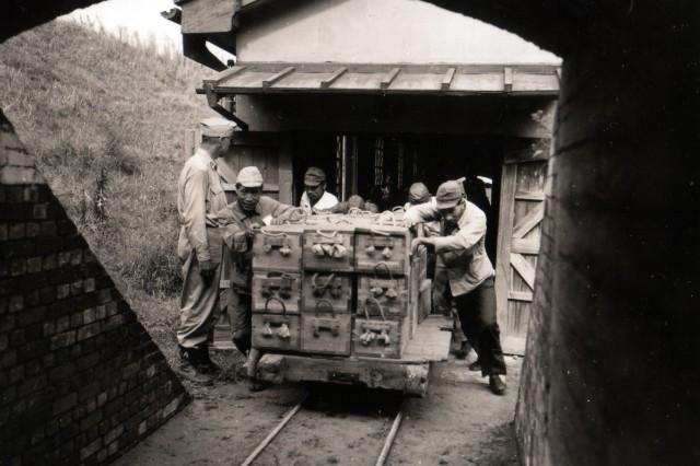 Japanese men removing ammunition from the Hiratsuka Naval Powder Factory at Hiratsuka, Japan.