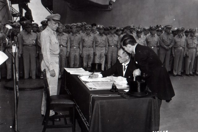 Namoro Shigomitso signs on behalf of the Emperor of Japan and the Japanese Imperial government during the surrender ceremony on the U.S.S. Missouri.  Lt. Gen. Richard Sutherland, U.S. Army Chief of Staff - Southwest Pacific Area, stands at the table. (September 2, 1945)