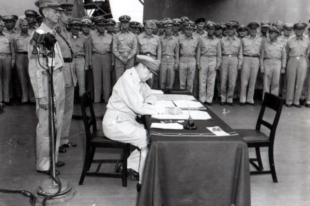 Gen. Douglas MacArthur signs the Instrument of Peace as Supreme Commander of the Allied Powers during the Japanese surrender ceremony aboard the U.S.S. Missouri.  Behind General MacArthur are Lt. Gen. Jonathan Wainwright (left) and Lt. Gen. A.E. Percival, British Commander of Singapore. (September 2, 1945)