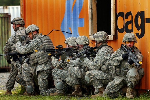 Soldiers prepare to clear a mock building.