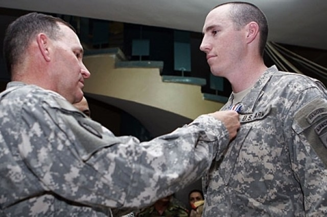 U.S. Army Maj. Gen. Benjamin Mixon, commander, 25th Infantry Division and Multi-National Division - North, pins the Silver Star on Capt. Brennan Goltry, platoon leader, 2nd Platoon, Company C, 2nd Battalion, 505th Parachute Infantry Regiment, 82nd Airborne Division, during a ceremony July 31, 2007, at Patrol Base Olson in Samarra, Iraq. Capt. Goltry also received two Purple Hearts and the Combat Infantryman Badge.