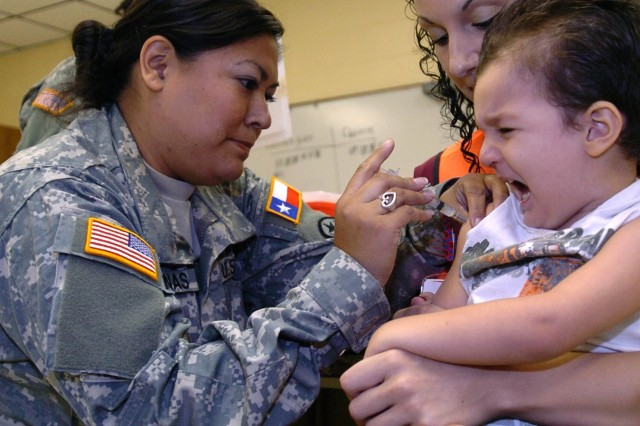 Army National Guard Spc. Stephanie Cardenas, an Emergency Medical Technician for Joint Forces Headquarters of San Antonio, gives a vaccination shot to 4-year-old Jeremiah Burkett while he\'s comforted by his mother. The boy will be ready for pre-kindergarten this fall, at least as far as immunizations go, thanks to the free vaccinations offered in Brownsville during Operation Lone Star.