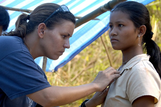 A medic examines a Laotian girl. In addition to searching for the remains of missing-in-action, the Soldiers provide medical care for area residents.