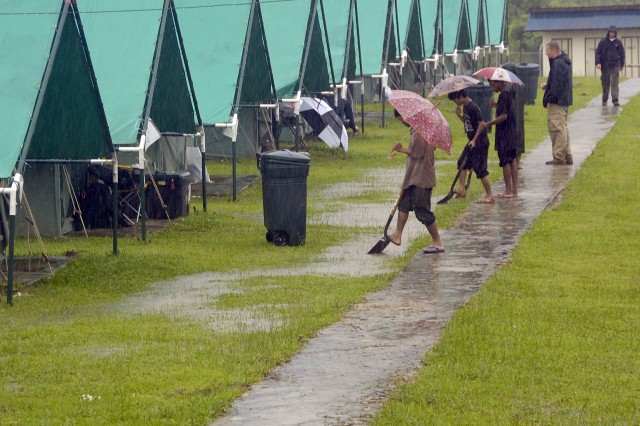 Workers dig a trench to prevent tents from being flooded.