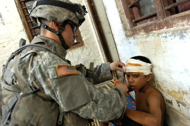 "Pvt. Francis Kianco of Troop A, 1st Squadron, 14th Cavalry Regiment, attached to the 2nd Brigade Combat Team, 1st Cavalry Division, prepares to redress a young boy's wounds caused by a car bomb. Kianco and members of the ""Death Stalker"" platoon found the boy in his home during a joint patrol with Iraqi soldiers in Baghdad's Karkh District"