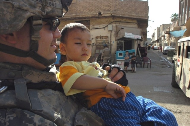 Pfc. Roger Montague of Troop A, 1st Squadron, 14th Cavalry Regiment, attached to the 2nd Brigade Combat Team, 1st Cavalry Division, hangs out with a new buddy during a joint patrol in Baghdad's Karkh District.