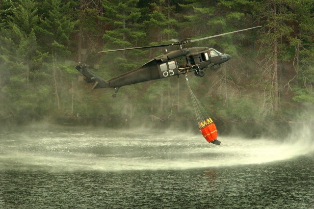 After dropping water on the fire using a remote-control device, the crew scoops up another bucket full. Fortunately, there are lakes in the area.