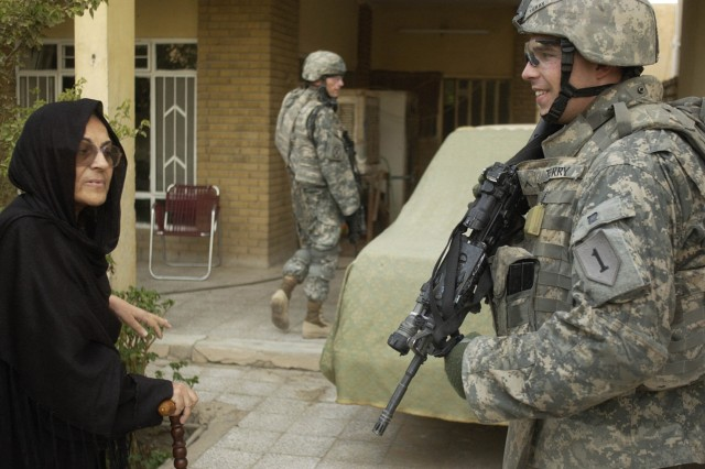 Pvt. Brian Terry, from the 1st Infantry Division, speaks with an Iraqi woman during a clearing operation in the Hateen district of Baghdad, July 26.