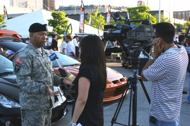 LTC Samuel Jones, USAR, gives an interview to an ABC-7 news Chicago reporter during Boost Mobile's Night Shift auto show at Chicago's Soldier Field.
