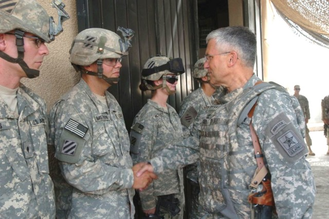 Army Chief of Staff Gen. George W. Casey Jr. presents Spc. Chris Armstrong, Headquarters Company, 1st Battalion, 15th Infantry Regiment, with a coin Aug. 11, at Patrol Base Assassin, Iraq. Gen. Casey visited Soldiers in Iraq and Afghanistan last week.