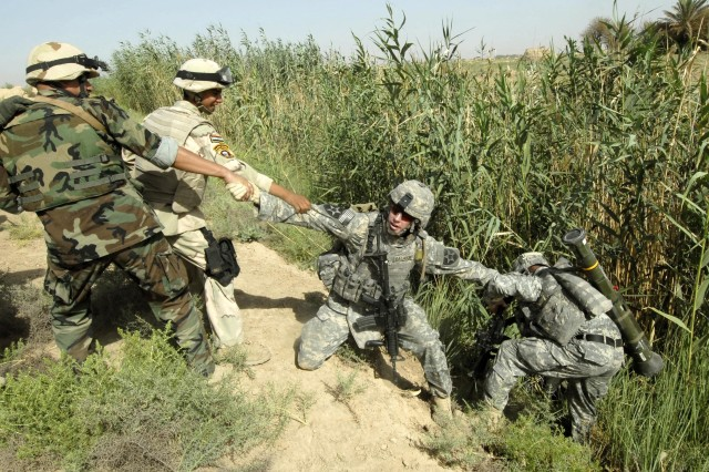 A U.S. Soldier who fell into an irrigation ditch is pulled out by fellow U.S. and Iraqi Soldiers.