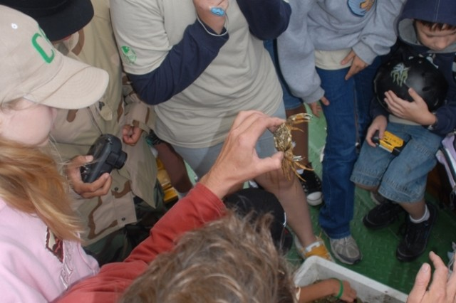 "Boat captain Bernd Laager shows Camp A.R.M.Y Challenge participants different sea creatures during a ""watten safari."""