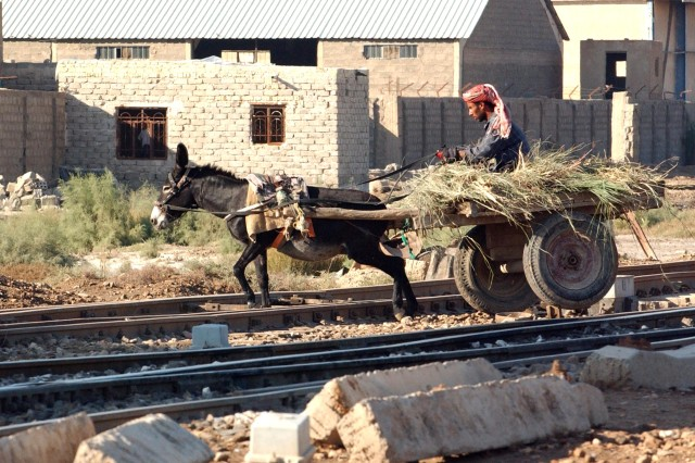 An Iraqi farmer crosses railroad tracks as nearby Latvian soldiers patrol Ad-Diwaniyah. Much of Iraq's agricultural and economic development is still primitive by 21st-century Western standards.