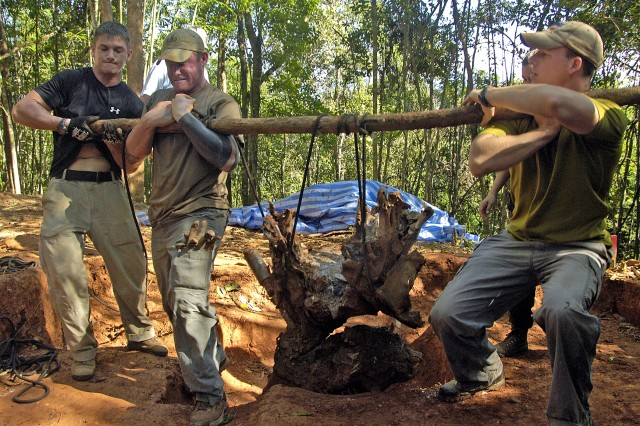 Members of the Joint POW/MIA Accounting Command work together to remove wreckage from a crash site in Xekong Province, Laos, on July 24. A 10-member JPAC team including a forensic anthropologist, life support investigator, explosive ordnance disposal technician and field medic worked in Laos for a month attempting to recover the remains of pilots that crashed in the area during the Vietnam War.