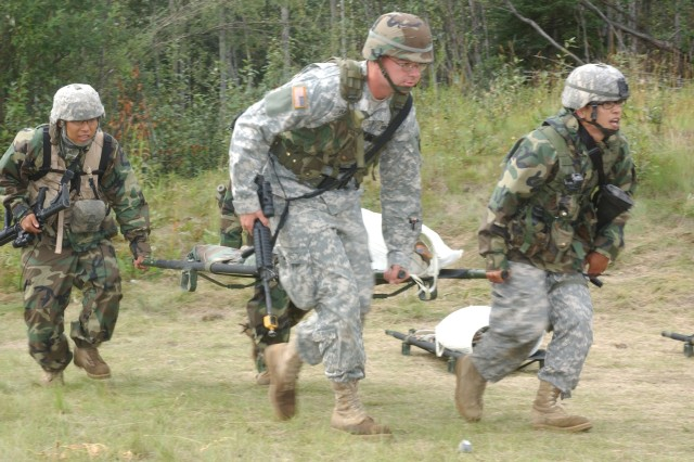 Soldiers rush a role-playing wounded Soldier to an awaiting UH-60 Black Hawk helicopter.