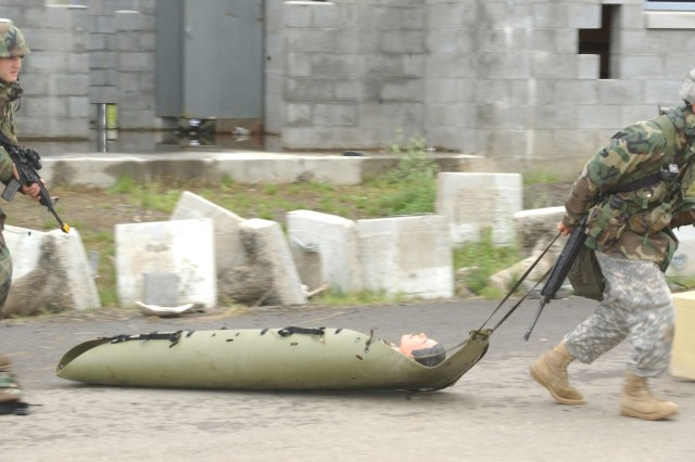 Soldiers move a role-playing wounded Soldier away from the line of fire.