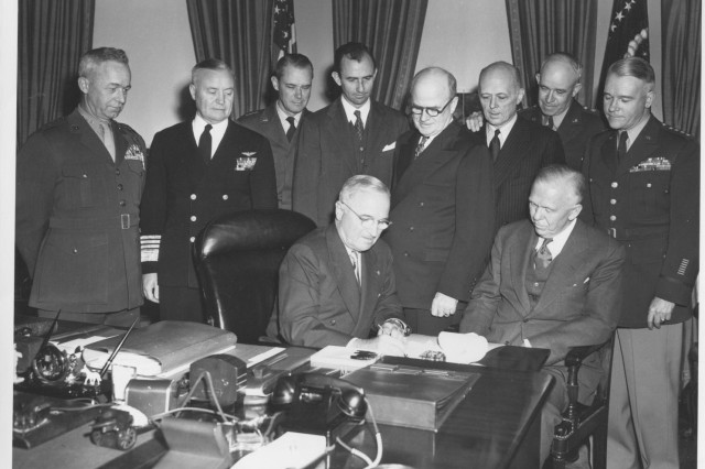 President Harry Truman signs a proclamation making May 19 Armed Forces Day, April 2, 1951.  At the time of this photograph, the Army had been operating the nation's railroads for over seven months.  Secretary of the Army Frank Pace, Jr., stands directly behind Truman, fourth from the left.  Other notables in the image:  Secretary of Defense George C. Marshall sits to the right of Truman; Gen. of the Army Omar Bradley, Chairman of the Joint Chiefs of Staff, stands second from the right; and Gen. J. Lawton Collins, Chief of Staff, U.S. Army, stands at the far right.