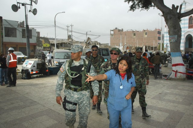 Pfc. David Torres gets a briefing on the situation in the town of Pisco from Maricarmen Perez, a local paramedic