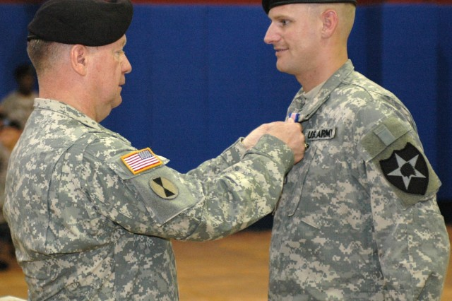 Maj. Gen. James A. Coggin, 2nd Infantry Division commander, presents Pfc. Russell McCanless Jr., Headquarters and Headquarters Support Company, Division Special Troops Battalion, with the Soldier's Medal Aug. 16 at Camp Red Cloud, Korea. Pfc. McCanless and Pfc. Reid Erickson, HHSC, DSTB, rescued an elderly woman and her physically handicapped daughter from their burning apartment.