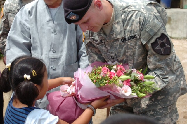 Pfc. Russell McCanless Jr. receives flowers from the children of Seon Jae Dong Ja Buddhist Orphanage in Uijeongbu, Korea. Pfc. McCanless and Pfc. Reid Erickson donated the anonymous award money they received for rescuing two women from a fire to the orphanage.