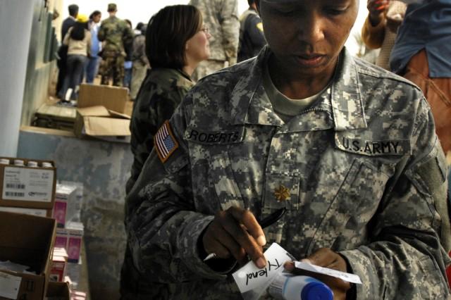 Maj. Sonya Roberts prepares medicine to give to a family.