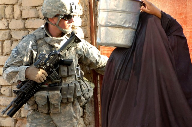 While conducting a foot patrol Aug. 14, in support of Operation Lightning Hammer in Mukeisha, Iraq, Sgt. Nic Root holds the door open for a local resident carrying water from a nearby canal. Sgt. Root is from Headquarters and Headquarters Troop, 5th Squadron, 73rd Cavalry Regiment, 3rd Brigade Combat Team, 1st Cavalry Division.