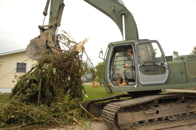 Sgt. Jay E. Haaland clears large trees and branches using a hydraulic excavator.